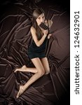 Pretty young woman nibbling the bar of chocolate, view from above, brown background - stock photo