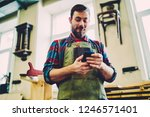 positive male joiner in apron... | Shutterstock . vector #1246571401