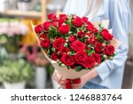 Stock photo bouquet in the hands of a cute girl garden red spray roses color passionately scarlet autumn mood 1246883764
