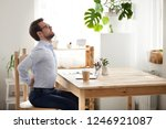 Small photo of Tired millennial office worker stretch in chair suffer from sitting long in incorrect posture, male employee have back pain or spinal spasm working in uncomfortable position. Sedentary life concept