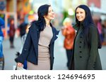 happy female friends walking the crowded city street - stock photo