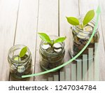 Small photo of Plant growing from coins money in glass jar on wooden table, increasing arrow up trend and rectangular chart with copy space provide, savings or investing concept