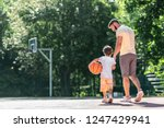 young family with a ball on the ... | Shutterstock . vector #1247429941