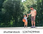 father and son with a ball on... | Shutterstock . vector #1247429944