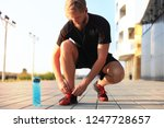 young handsome athlete tying... | Shutterstock . vector #1247728657