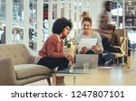 two businesswomen looking at a... | Shutterstock . vector #1247807101