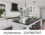 Stock photo beautiful kitchen in new luxury home features black counters and island with white woodwork and 1247887507