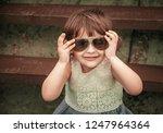 happy little girl in sunglasses | Shutterstock . vector #1247964364