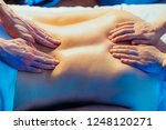 Small photo of Concept of healthcare and female beauty. Toned image. Two masseuses make a double back massage of a girl in a spa salon. hands view from the top