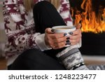young woman sitting and warming ... | Shutterstock . vector #1248223477
