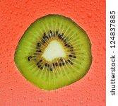 Fresh slice of kiwi fruit on red background drops - stock photo