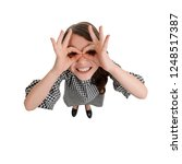 Small photo of Funny girl making finger glasses. Playful and impish mood. Top view, full length portrait.