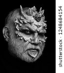 Small photo of Demon head isolated on black. Monster with sharp thorns and warts on face. Alien or reptilian makeup. Horror and fantasy concept. Man with dragon skin and grey beard.