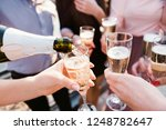 a young company pouring... | Shutterstock . vector #1248782647