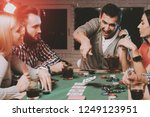 young friends playing poker on...   Shutterstock . vector #1249123951