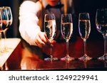 the bartender pours champagne.... | Shutterstock . vector #1249229941