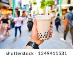 hand holding a plastic glass of ... | Shutterstock . vector #1249411531