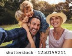 cheerful family making selfie.... | Shutterstock . vector #1250199211