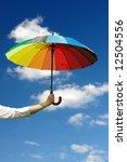Female hand holding multicolored umbrella against the sunny sky - stock photo