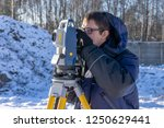 A surveyor conducts a topographical survey for the cadastre at a construction site in winter