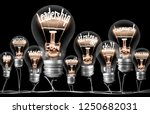Small photo of Photo of light bulbs group with shining fibers in a shape of LEADERSHIP concept related words isolated on black background