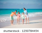 young family of four on beach... | Shutterstock . vector #1250784454