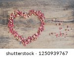 Stock photo pink petals shape heart on wood background mexican creeper antigonon leptopus or coral bells 1250939767