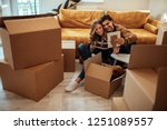 couple packing up boxes for... | Shutterstock . vector #1251089557