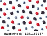 Fruit pattern of colorful wild berries isolated on white background. Raspberries, blueberries and blackberries. Top view. Flat lay