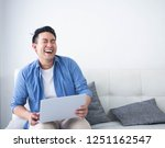 happy asian man using laptop in ... | Shutterstock . vector #1251162547
