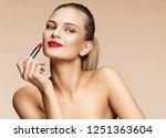 woman applying red lipstick.... | Shutterstock . vector #1251363604