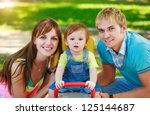 baby with parents in a green ... | Shutterstock . vector #125144687