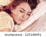 beautiful girl lying in bed at... | Shutterstock . vector #125148491