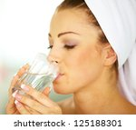 Portrait of a young female wrapped in a towel and drinking a glass of water - stock photo