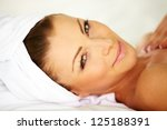 Portrait of a happy smiling young lady lying down at the spa - stock photo