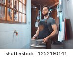 a young brewer in an apron... | Shutterstock . vector #1252180141