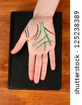 Small photo of Chiromancy.Color contours on palm, on wooden background