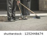 Municipal worker sweeping the...