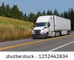 Small photo of White modern bonnet professional technological big rig semi truck transporting dry van semi trailer with commercial cargo on the road with trees and summer meadow background