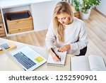 woman writing down notes while... | Shutterstock . vector #1252590901