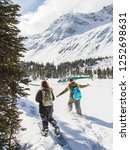 Two female hikers snowshoeing to a helicopter in the Canadian Rockies. Adventure tourism between Banff and Jasper National Parks in Alberta. Ultimate exploration deep in the mountains.