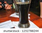 pint glass filled with dark... | Shutterstock . vector #1252788244