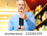 Man analyzing a bootle of red wine in a supermarket - stock photo