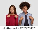Photo of desperate indignant two women point at each other with indignant expressions, recieve unexpected task, stand closely to each other, isolated over white background. Negative feeling concept