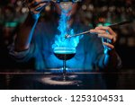 Stock photo bartender girl adding to a brown cocktail and pour on a flamed badian on tweezers a powdered sugar 1253104531