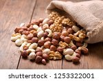 mix of nuts in a sack on wooden ... | Shutterstock . vector #1253322001