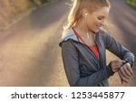 fitness woman looking at her... | Shutterstock . vector #1253445877