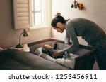 mother putting her baby to...   Shutterstock . vector #1253456911