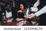 waiter pouring wine to glass... | Shutterstock . vector #1253908174