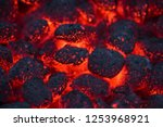 Small photo of Coals smolder and glow. Residual flame from smoldering coals in cinder, closeup view. Flicker of burning coals at night.